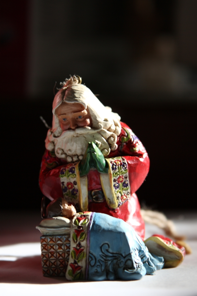 Santa Claus kneels before the Christ child