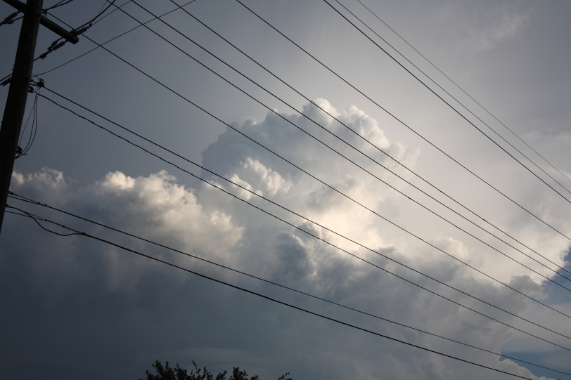 storm clouds behind telephone lines in color
