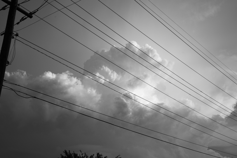storm cloud behind telephone lines in monochrome