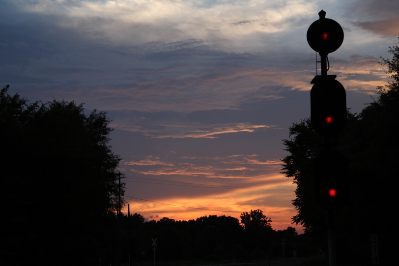 sunset by railroad signal